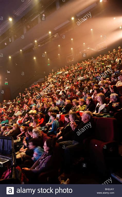 A full theatre audience sitting in auditorium watching a
